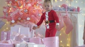 Poco muchacha divertida en los pijamas Santa Claus presenta los regalos debajo del árbol de navidad metrajes