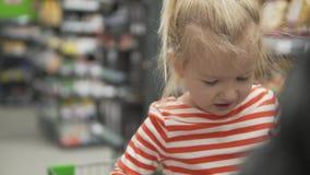 Poco muchacha divertida monta una carretilla en un supermercado almacen de metraje de vídeo