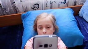 Poco muchacha hermosa juega en el teléfono y canta una canción que miente en la cama metrajes
