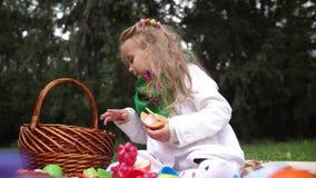 Poco muchacha hermosa se juega con los juguetes plásticos en parque del otoño 4K Cámara lenta metrajes