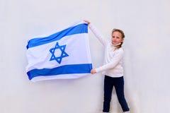 Poco muchacha judía del patriota con la bandera de Israel en el fondo blanco imagenes de archivo