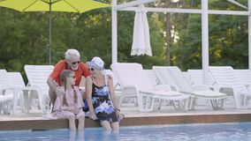 Poco muchacha linda con las coletas y la mujer madura que se sientan al borde de la piscina con sus pies en el agua almacen de video