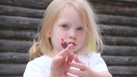 Poco muchacha linda con los ojos azules sostiene un flotador rojo para una caña de pescar almacen de video
