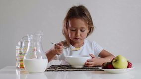 Poco muchacha linda del niño come con los copos de maíz del placer con leche almacen de metraje de vídeo