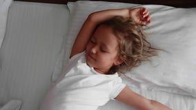 Poco muchacha linda es que despierta y que estira en cama en la mañana almacen de video