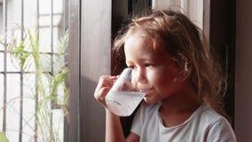 Poco muchacha linda está bebiendo su bebida que mira la ventana metrajes