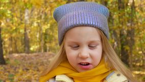 Poco muchacha linda está comiendo la manzana y está sonriendo en el parque en otoño almacen de metraje de vídeo