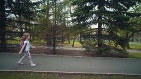 Poco muchacha linda está en el camino con los árboles de pino almacen de video