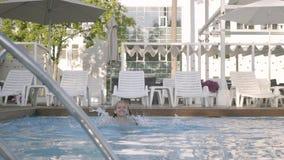 Poco muchacha linda nada en una piscina hermosa en un centro turístico costoso Reconstrucción y ocio al aire libre metrajes