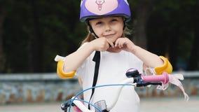 Poco muchacha linda pone en casco protector de la bicicleta almacen de video