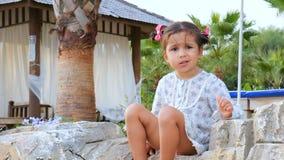Poco muchacha linda que habla consigo misma que se sienta en la playa metrajes