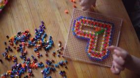 Poco muchacha linda que juega con el mosaico colorido