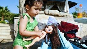 Poco muchacha linda que juega con una muñeca en la playa almacen de metraje de vídeo