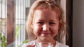 Poco muchacha linda sonriente est? bebiendo su bebida cerca de la ventana en casa metrajes