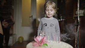 Poco muchacha linda sopla hacia fuera velas en partido de la torta de cumpleaños en casa almacen de metraje de vídeo
