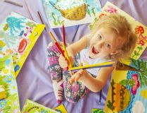 Poco muchacha pelirroja lanza los lápices coloreados entre su ryunok Visión desde arriba imagenes de archivo