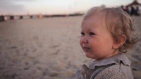 Poco muchacha rizada comió la arena insípida en la playa y los escupitajos y las torsiones almacen de video