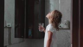 Poco muchacha rizada del niño aclara su boca con agua en el cuarto de baño, vista lateral metrajes