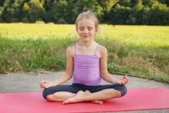 Poco muchacha rubia que hace el tablón de los ejercicios de la aptitud en el parque fotografía de archivo libre de regalías