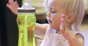 Poco muchacha rubia salpica con una botella en un café almacen de video