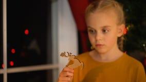 Poco muchacha sola que juega con el juguete de madera cerca de ventana en el orfelinato, víspera de Navidad almacen de video