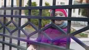 Poco muchacha sonriente 3-4 años que suben en la cerca almacen de metraje de vídeo