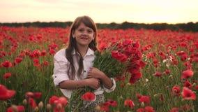 Poco muchacha sonriente con el ramo de amapolas rojas que se colocan en campo florecido en la puesta del sol almacen de video