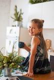 Poco muchacha sonriente que sostiene un casquillo que se sienta en la tabla en cocina en decoraciones de la Navidad imagen de archivo