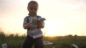 Poco muchacho alegre con una pila grande de dinero en naturaleza en la puesta del sol en la cámara lenta almacen de video