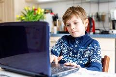 Poco muchacho del niño de la escuela que hace la preparación de la escuela en el ordenador Niño que se divierte con el aprendizaj Imagen de archivo libre de regalías