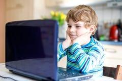 Poco muchacho del niño de la escuela que hace la preparación de la escuela en el ordenador Niño que se divierte con el aprendizaj Imagen de archivo