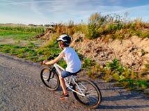 Poco muchacho del ni?o en el casco blanco que monta su bicicleta imagenes de archivo