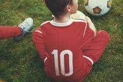 Poco muchacho delantero del jugador del fútbol que se sienta en hierba Fotos de archivo libres de regalías