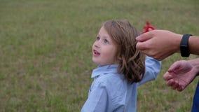 Poco muchacho lindo 5 años con el pelo largo que vuela una cometa, aire libre del verano almacen de metraje de vídeo
