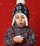 Poco muchacho lindo del niño está sosteniendo nieve en las manos que llevan la ropa caliente y el sombrero aislados en fondo rojo imagenes de archivo