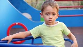 Poco muchacho lindo está haciendo girar en el carrusel en un parque de los niños en un día de verano soleado almacen de video