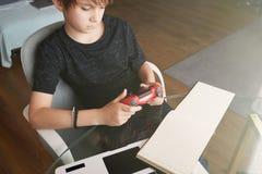 Poco muchacho lindo que juega la consola del videojuego asentada en sala de estar en casa imagenes de archivo