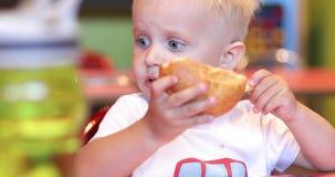 Poco muchacho rubio que come un pan en un café almacen de metraje de vídeo