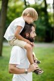 Poco muchacho rubio que lleva una camiseta blanca que se sienta en los hombros de su padre barbudo hermoso imagen de archivo libre de regalías