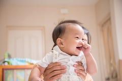 Poco neonato di Asain 7 mesi con il dito del pollice nella bocca Fotografia Stock