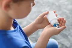 Poco niño con las píldoras en casa Peligro de la intoxicaci?n del medicamento fotografía de archivo