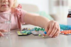 Poco niño con muchas diversas píldoras y agua en la tabla dentro Peligro de la intoxicaci?n del medicamento imágenes de archivo libres de regalías