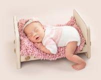 Poco niño en mono hecho punto en cama de bebé foto de archivo