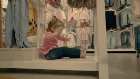 Poco niño, muchacha, se sienta en una tienda de ropa debajo de las ventanas, salpica y espera a su madre almacen de metraje de vídeo