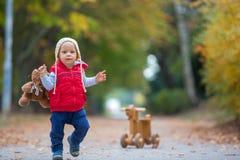 Poco niño pequeño con el oso de peluche, BI de madera de la balanza del perro que monta fotos de archivo libres de regalías