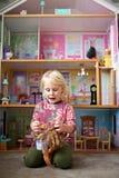 Poco niño que juega los juguetes delante de una casa de muñecas grande en su dormitorio imagen de archivo libre de regalías