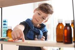 Poco niño que toma píldoras del estante Peligro de la intoxicaci?n del medicamento fotos de archivo