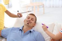 Poco niños que pintan la cara de su padre mientras que él que duerme en el sofá en casa fotografía de archivo