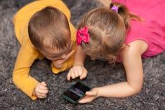 Poco niños usando smartphone en casa foto de archivo