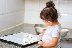 Poco ni?a peque?a que hace la panader?a de la torta en cocina foto de archivo libre de regalías